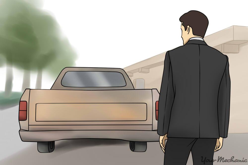 man standing next to a beat up truck