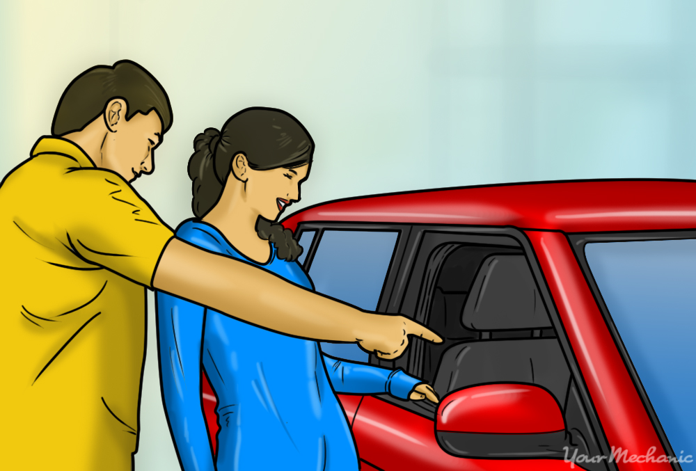 parent and teenager looking at a car