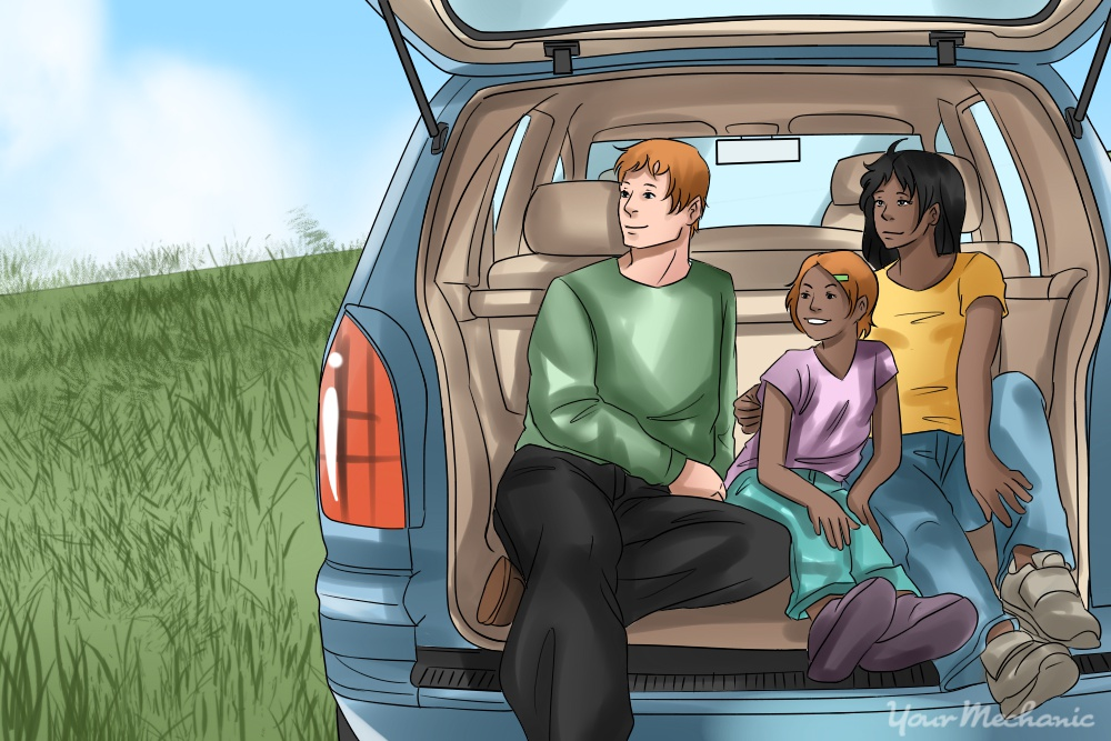 family sitting in SUV enjoying view