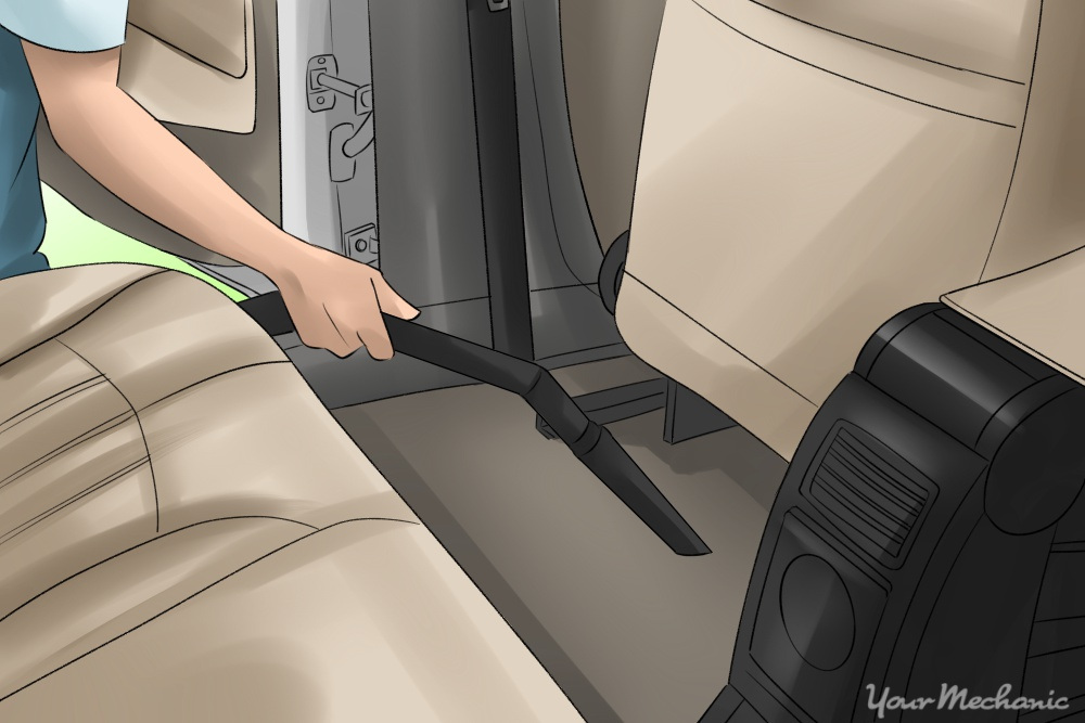 person vacuuming car with attachment for vehicles