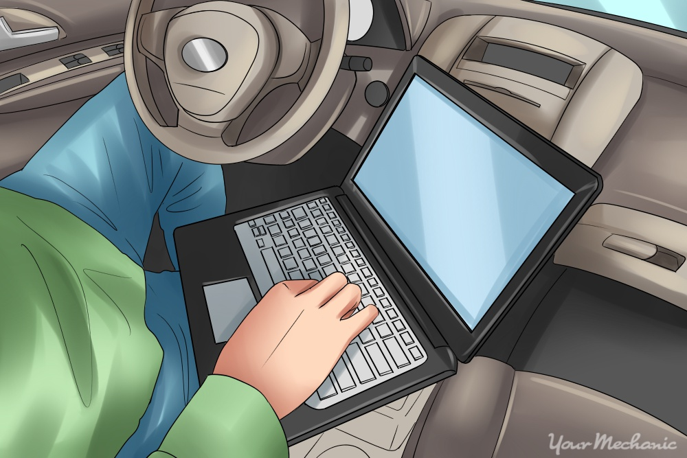mechanic sitting in a car on laptop