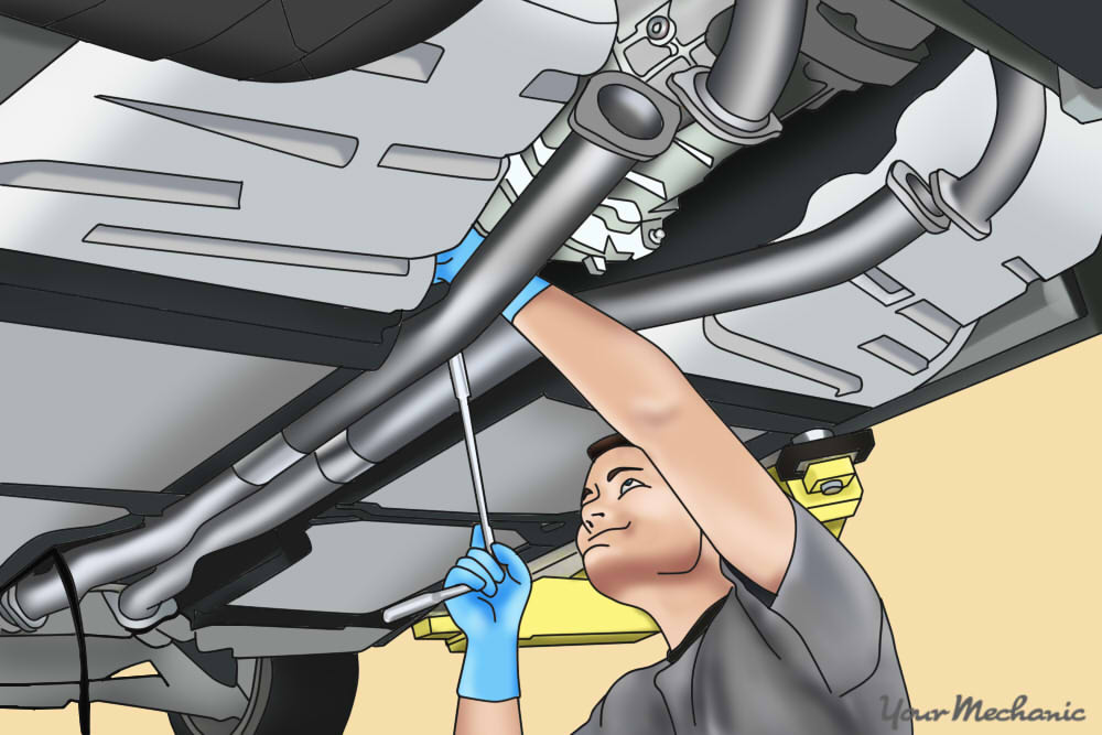 man installing exhaust system into car