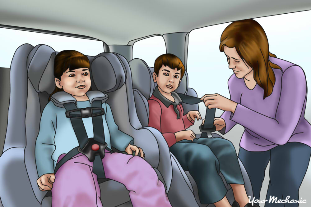 a mother buckling in her two kids into child seats
