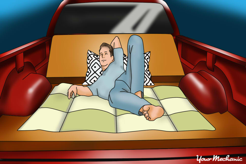 man laying in truck bed couch