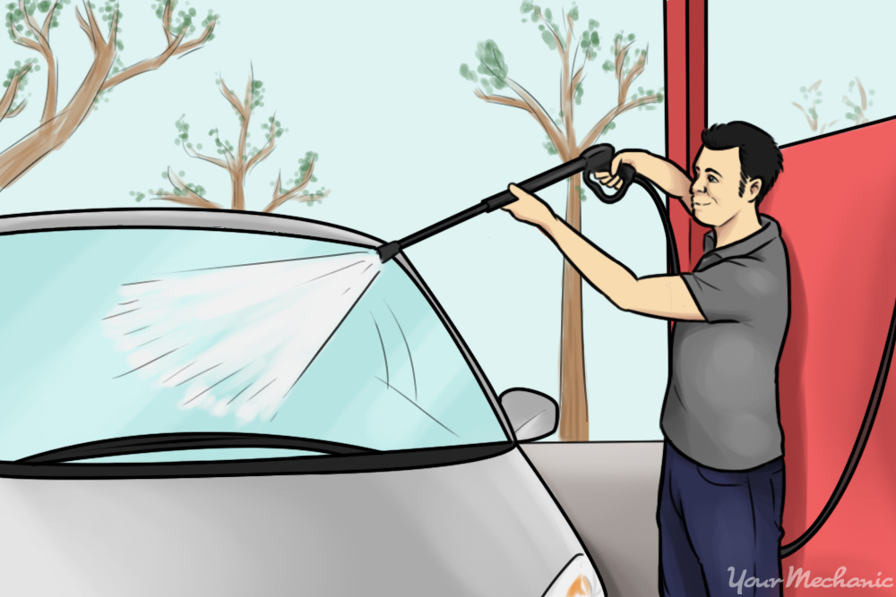 person using rinser at self service car wash