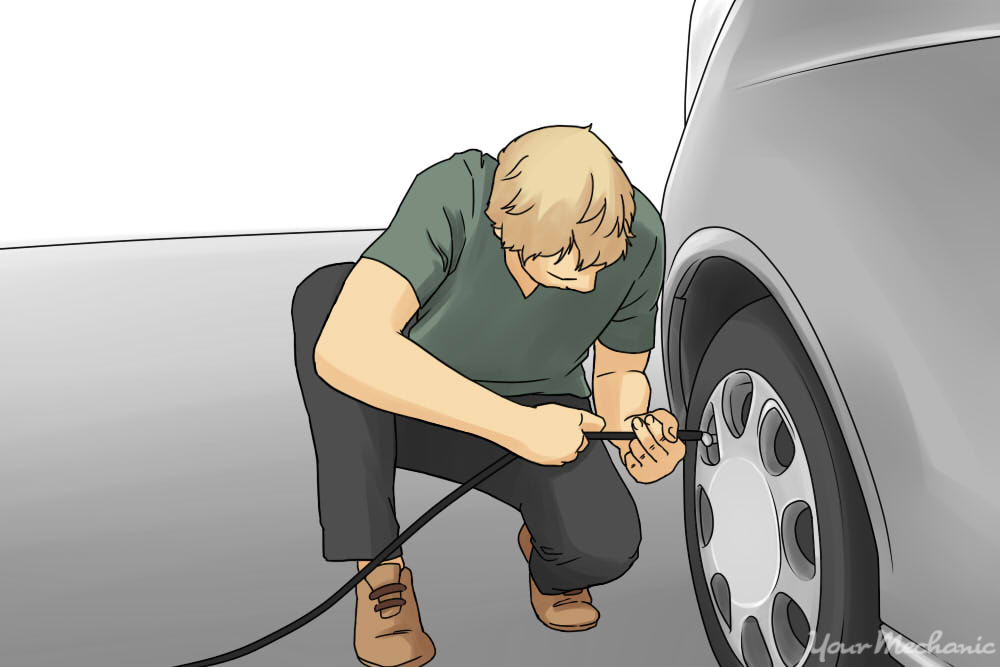 man kneeling down inserting air hose into tire