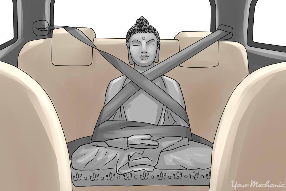 asian statue sitting in car