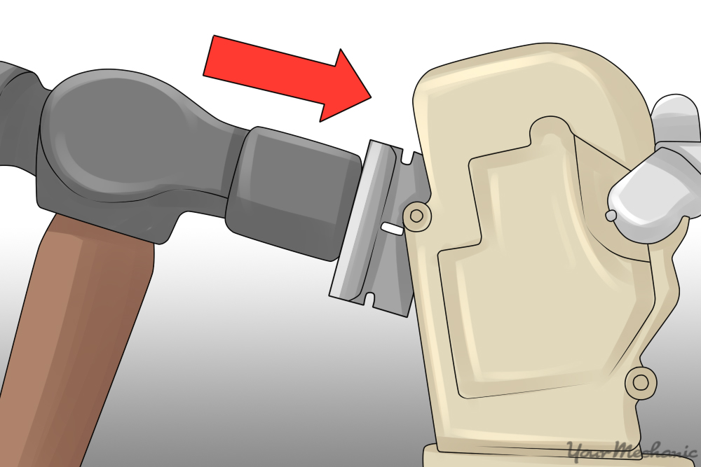 small hammer being used to tap the razor blade into the seam of the actuator