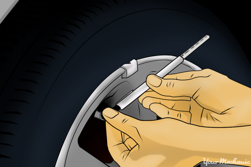 hands checking tire pressure gauge