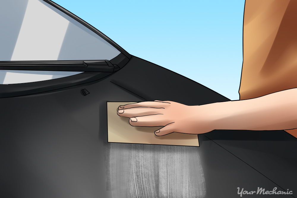 How to Properly Buff Clear Coat - A person sanding the hood of a car