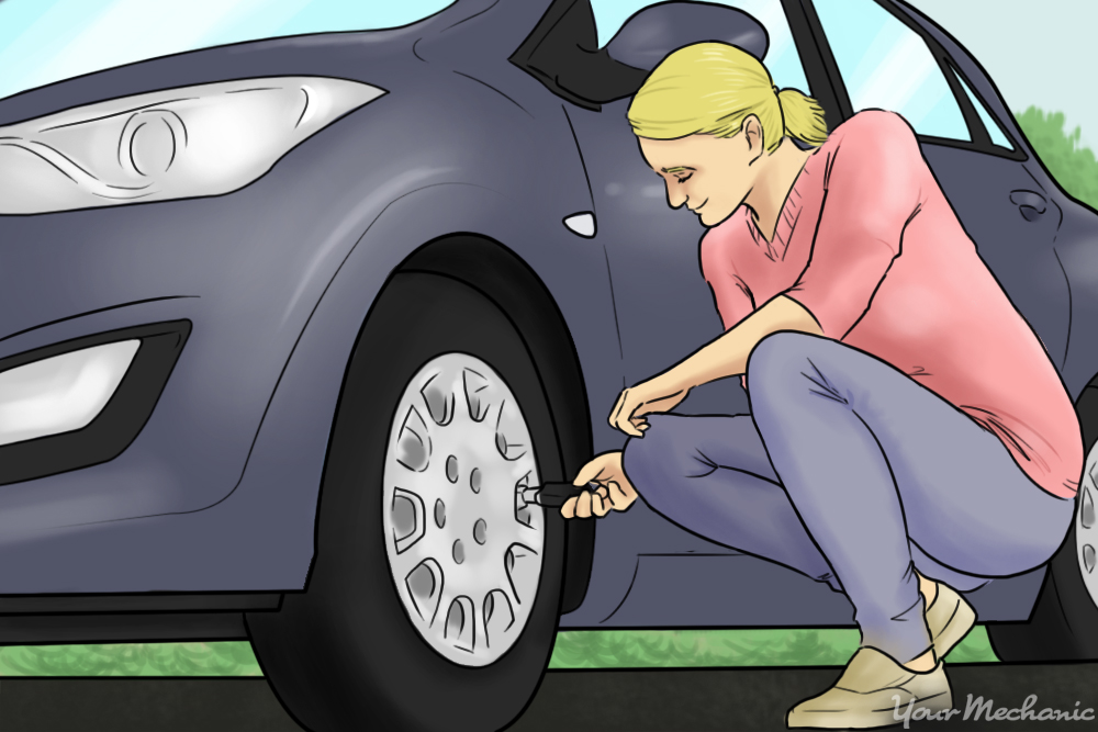 woman next to car checking tire pressure