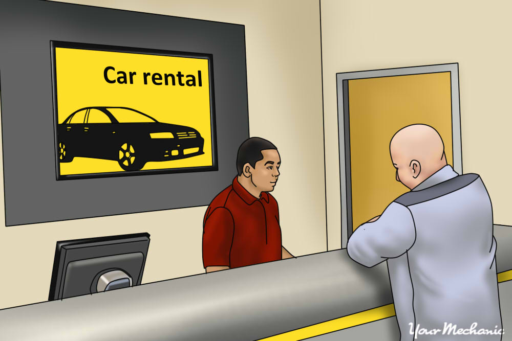 two people speaking at counter at rental car agency