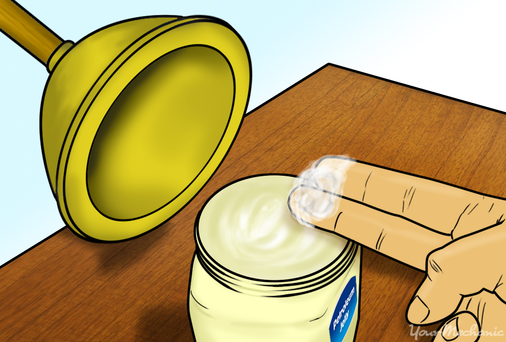 two fingers applying petroleum jelly to plunger