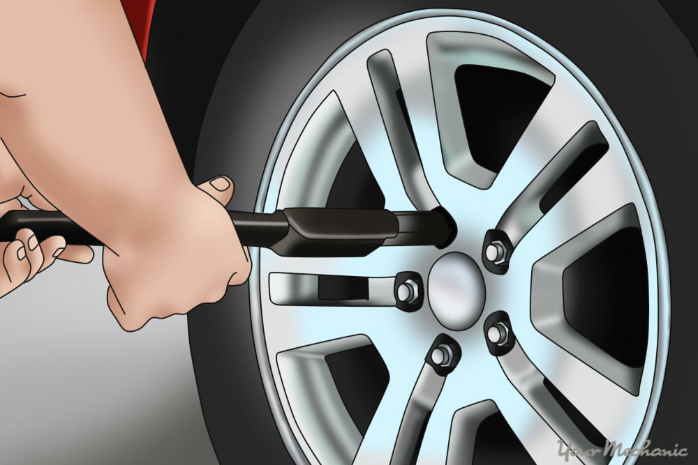 person loosening lug nuts on a car tire