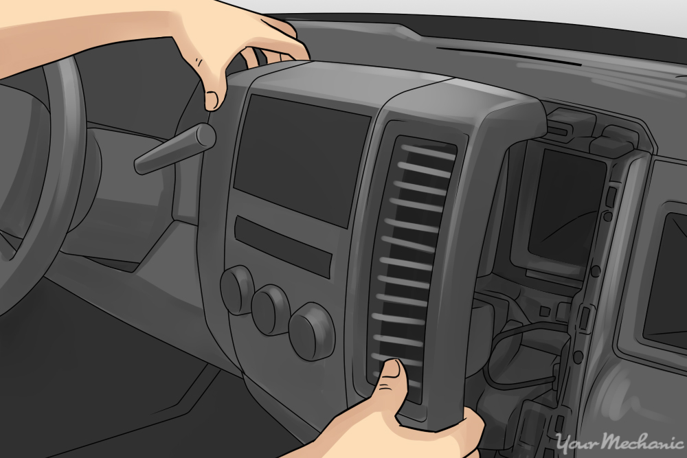 person taking apart a dashboard