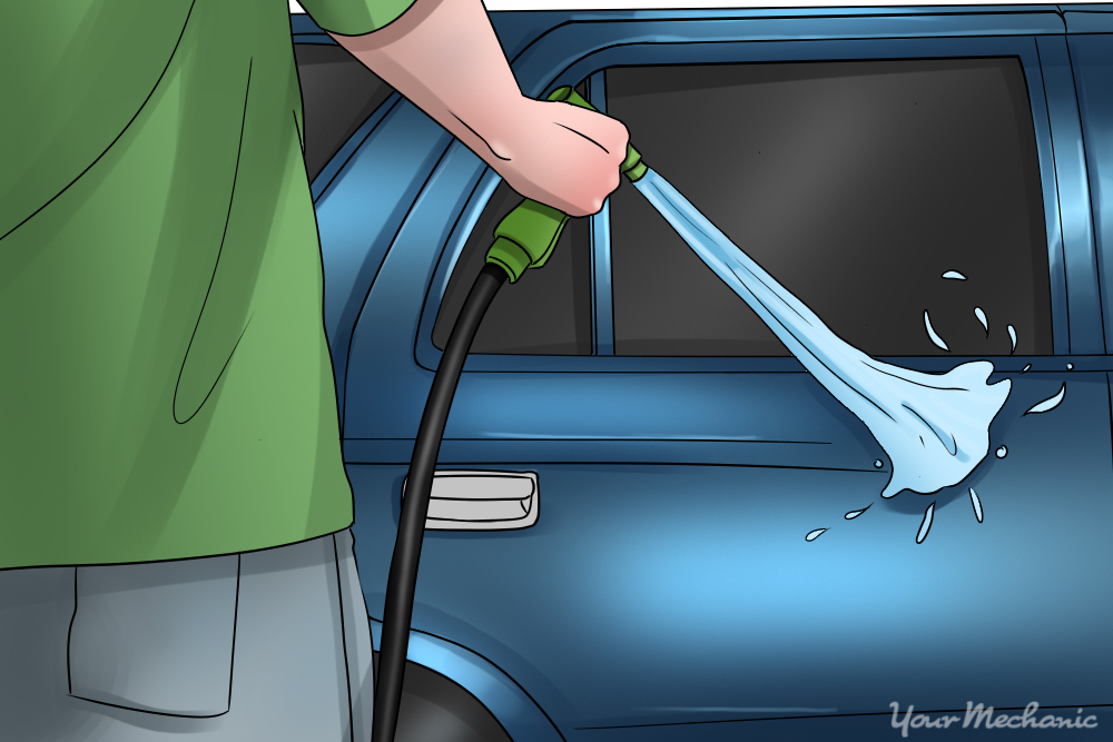 man spraying car with a hose