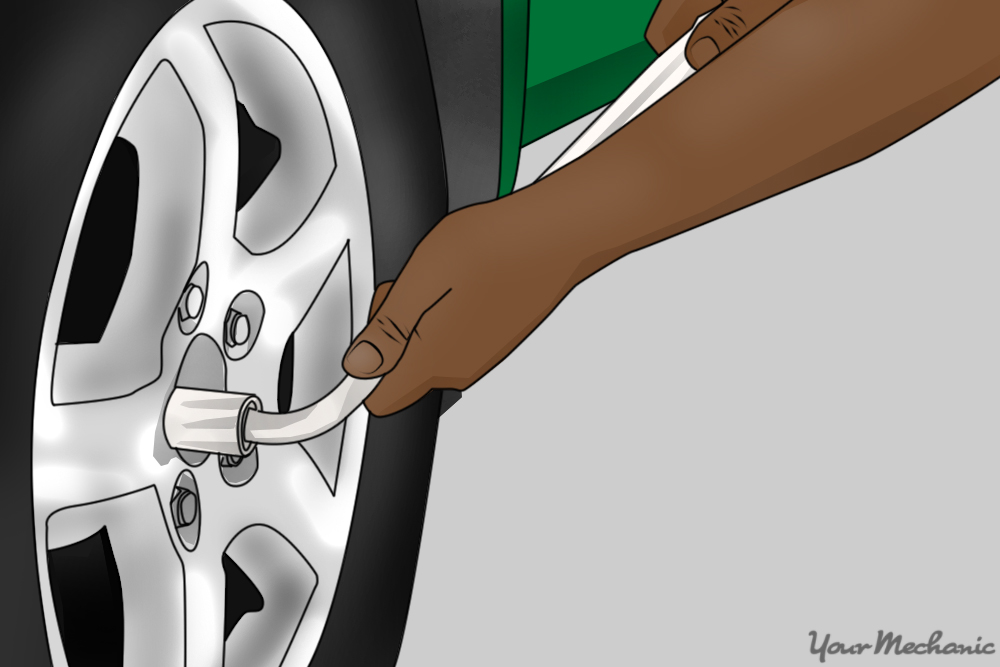 person using wrench to remove lug nuts