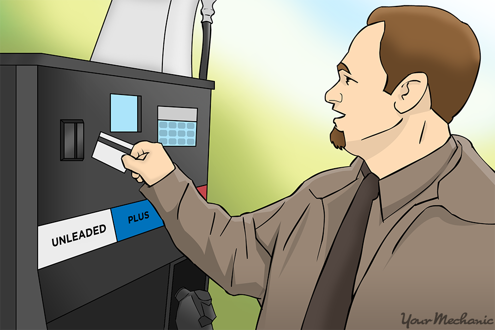 man inserting card into gas pump