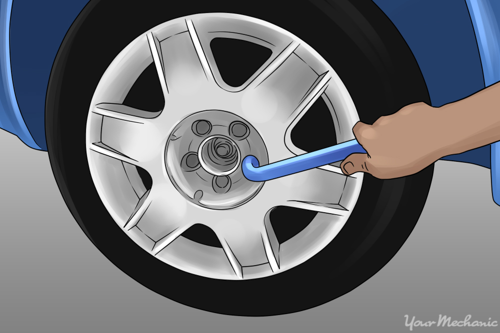 unbolting a tire from the vehicle using a ratchet an socket