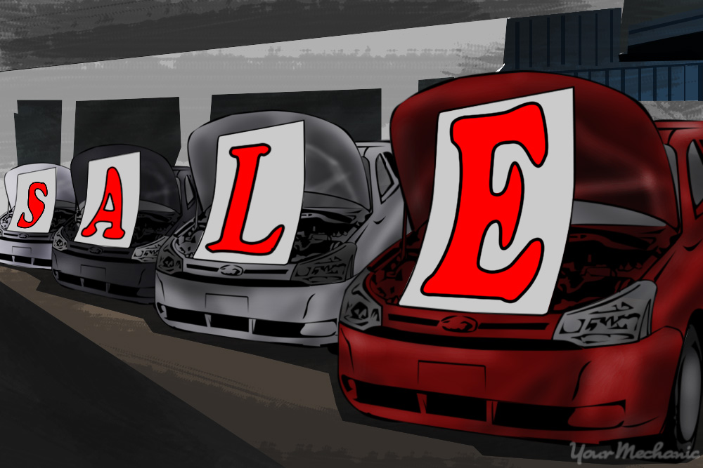 sale signs placed under car hoods