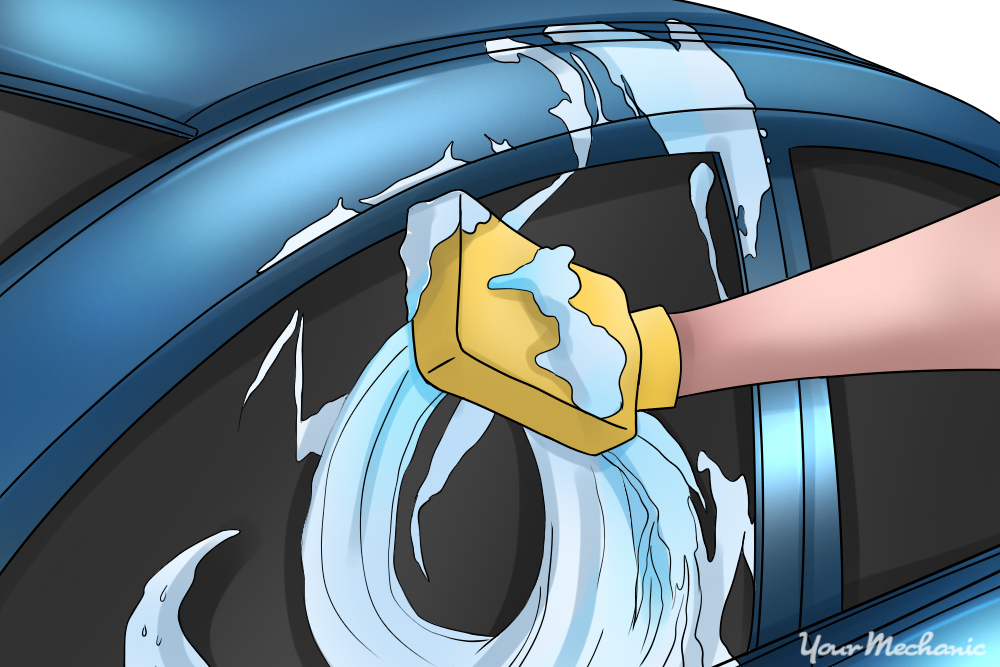 hand soaping up car with a wash mitt