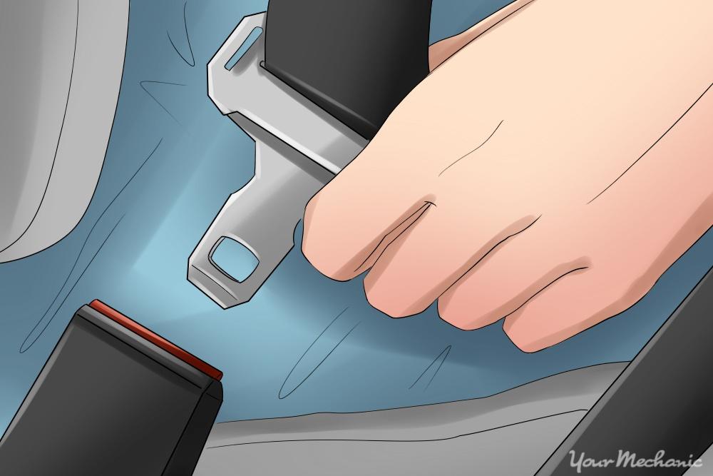 close up of hand unbuckling seat belt