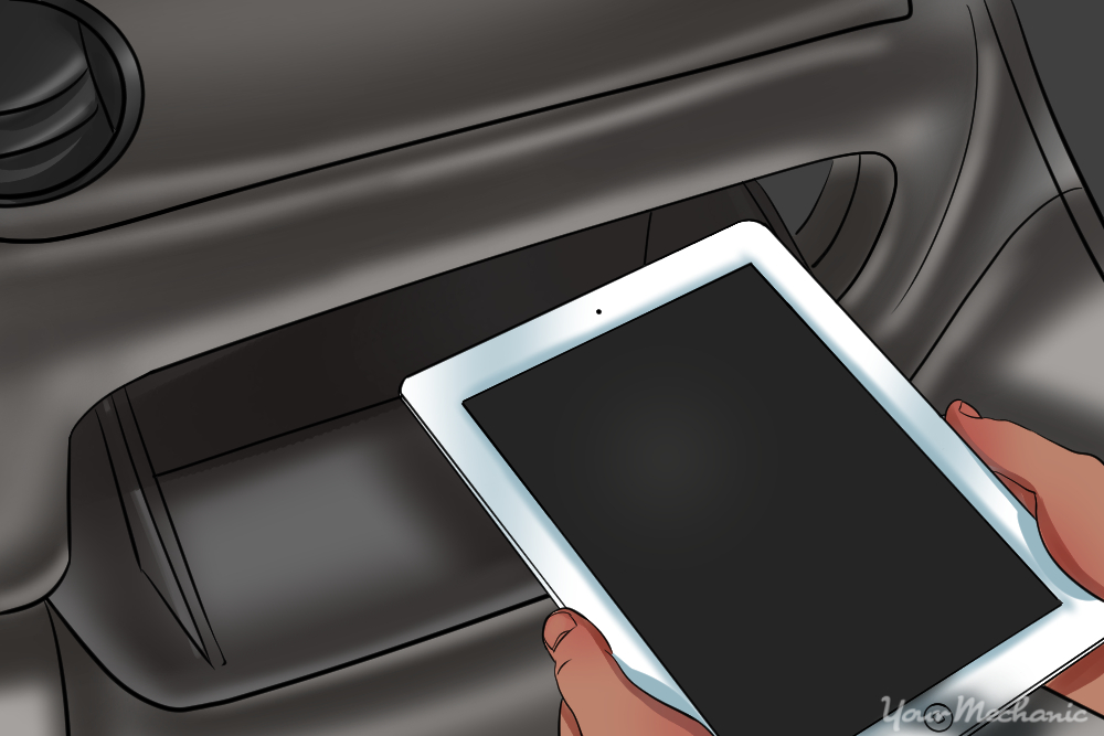 person placing tablet into their glove compartment