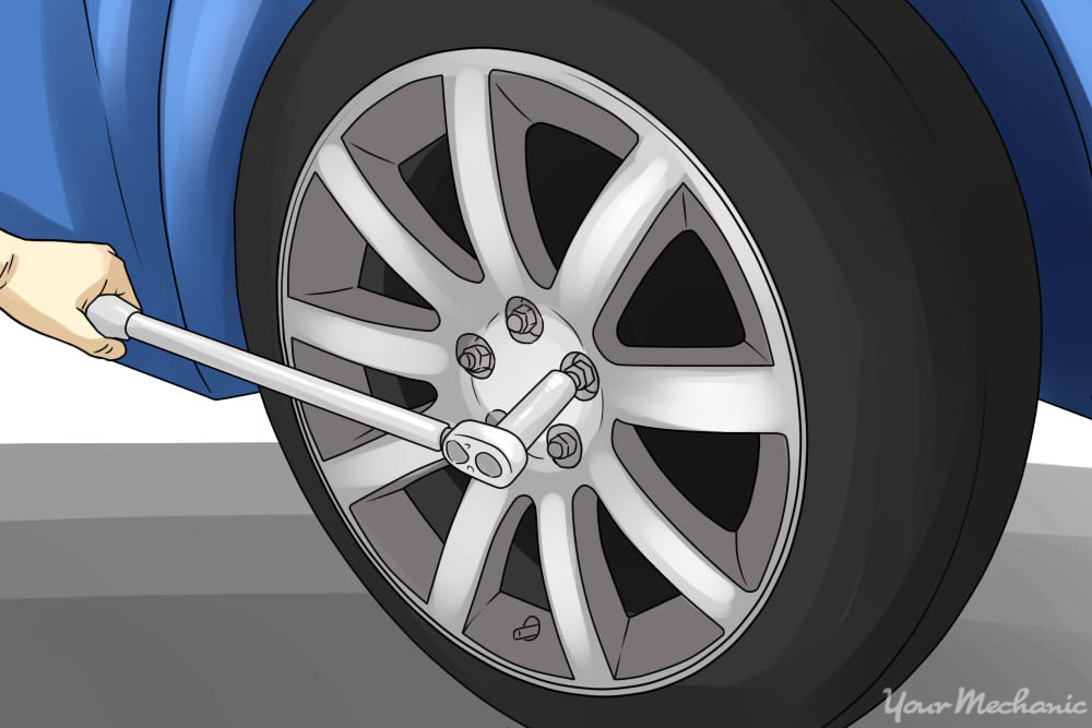 person loosening up their lug nuts on the wheel of car
