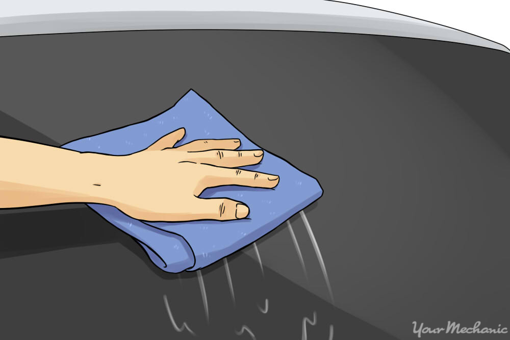 hand wiping off glass cleaner