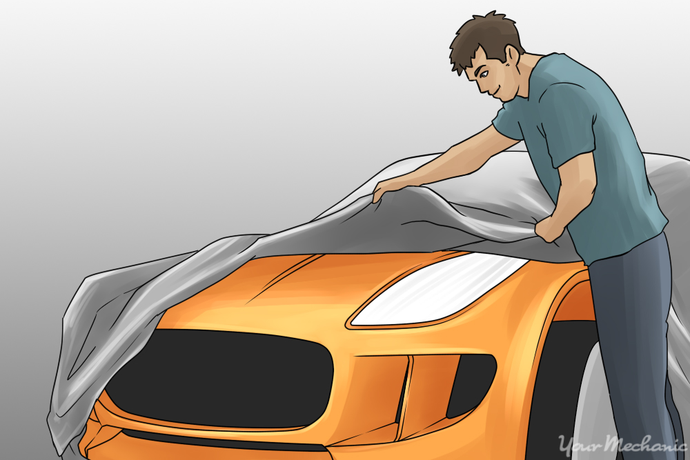 man placing a car cover on a vehicle