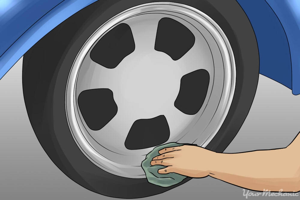 person using cloth to apply wheel wax