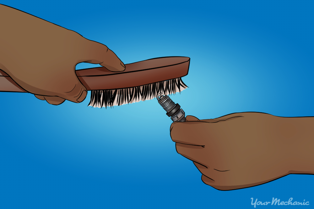 cleaning spark plug with a wire brush