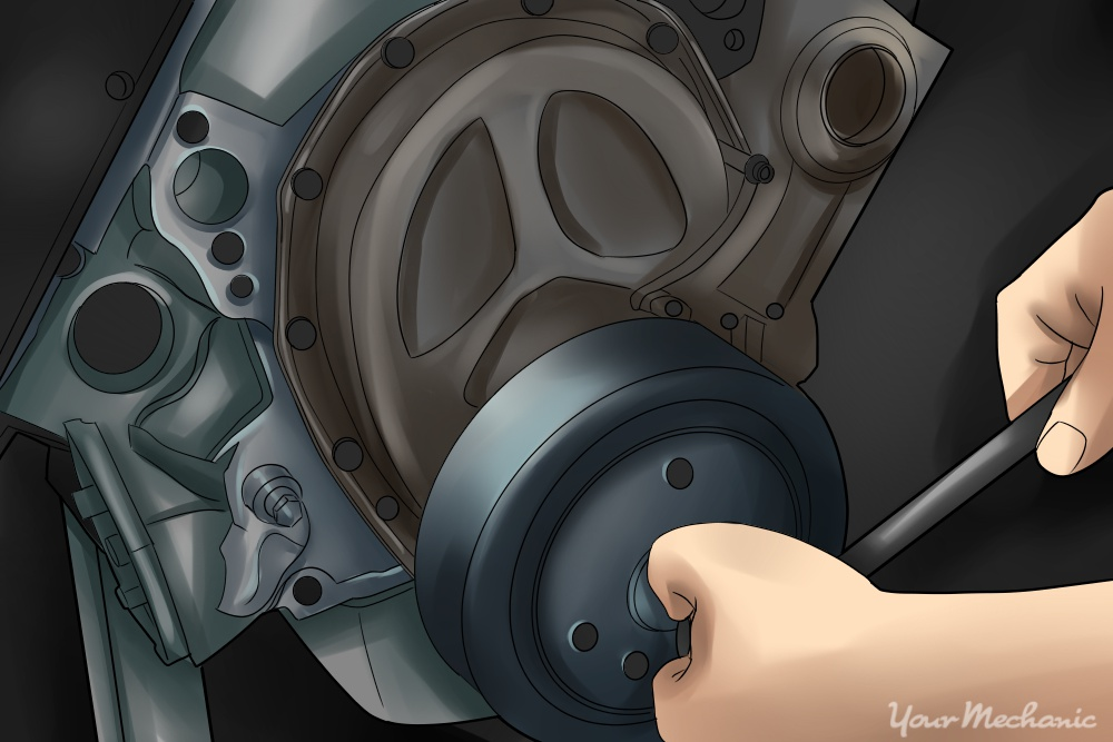 person turning crankshaft by hand with ratchet