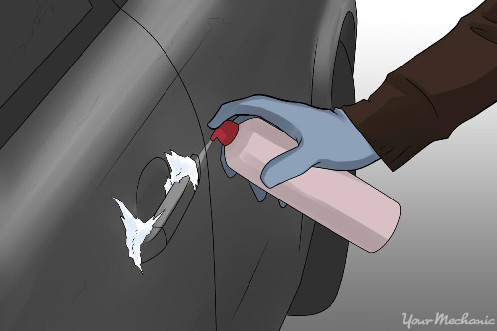 spraying de-icer on car