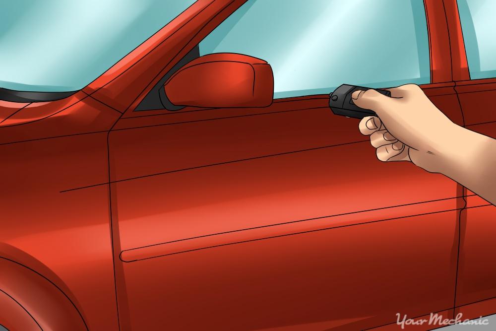 hand holding car alarm up to door