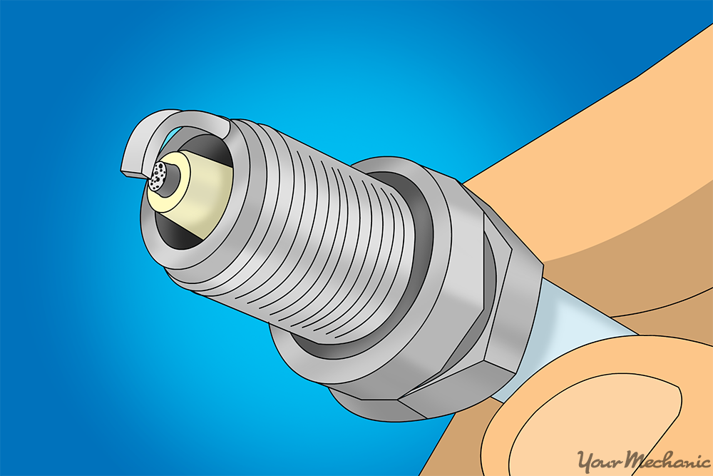 spark plug with black peppering over plug