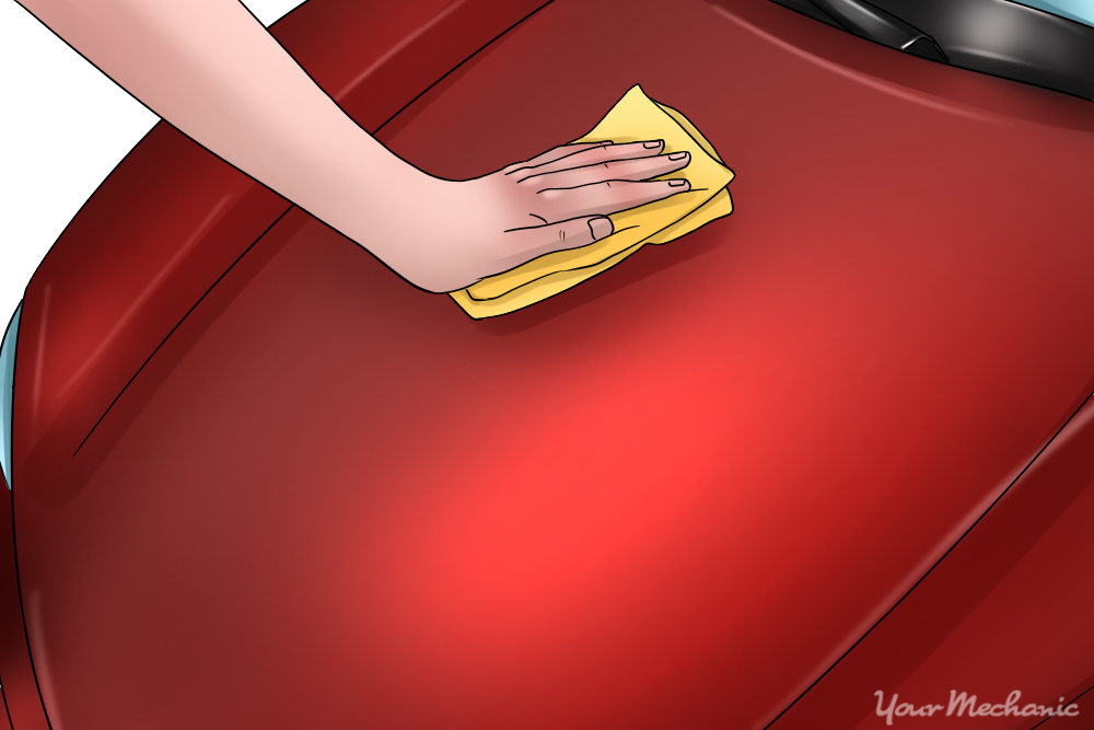 hand wiping cleaner onto car with cloth
