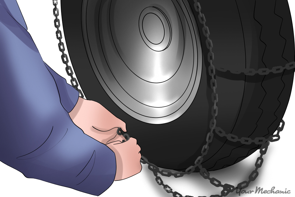 hands clamping c hook onto tire chain