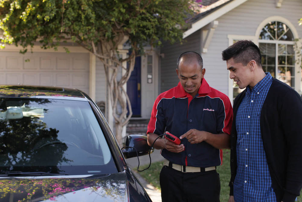 mechanic showing customer car in driveway