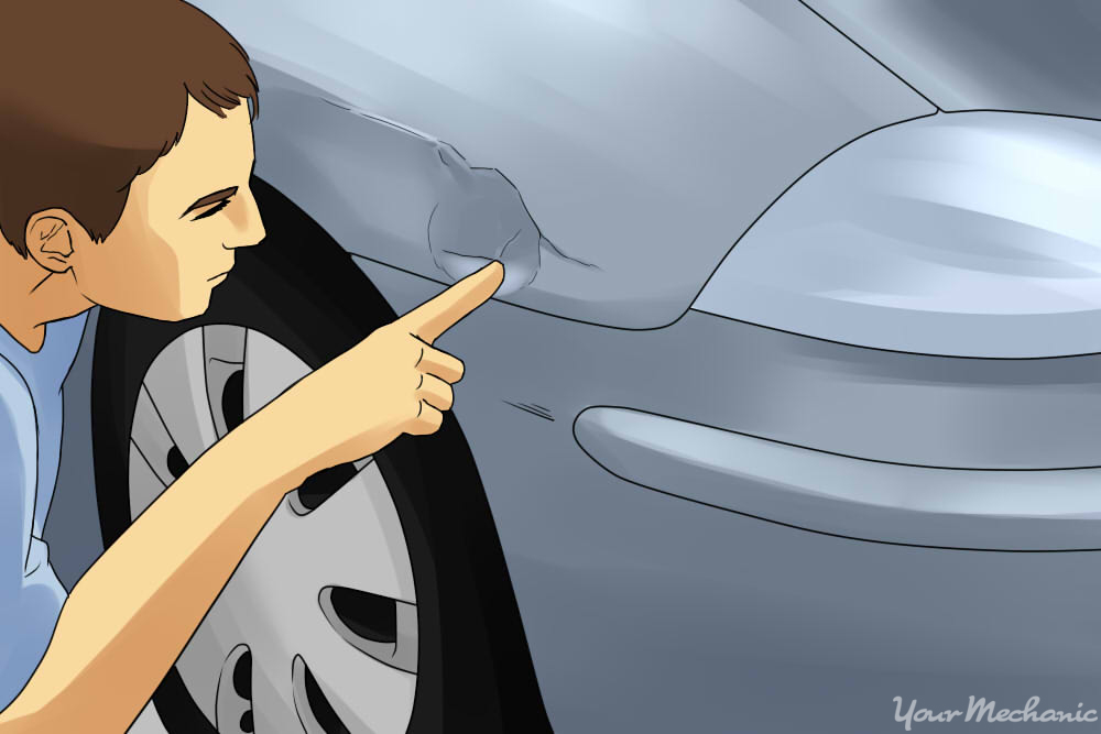 inspecting a dent on the side of a car