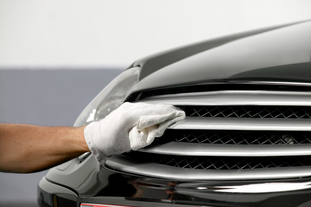 person polishing grille of black car