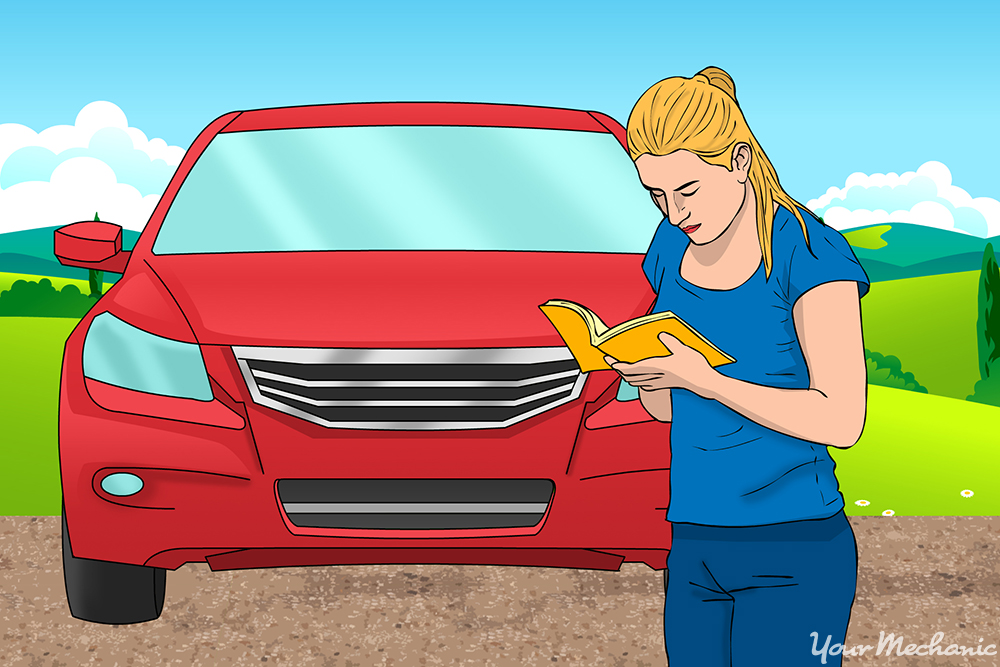 A woman in front of her car, reading the owner's manual