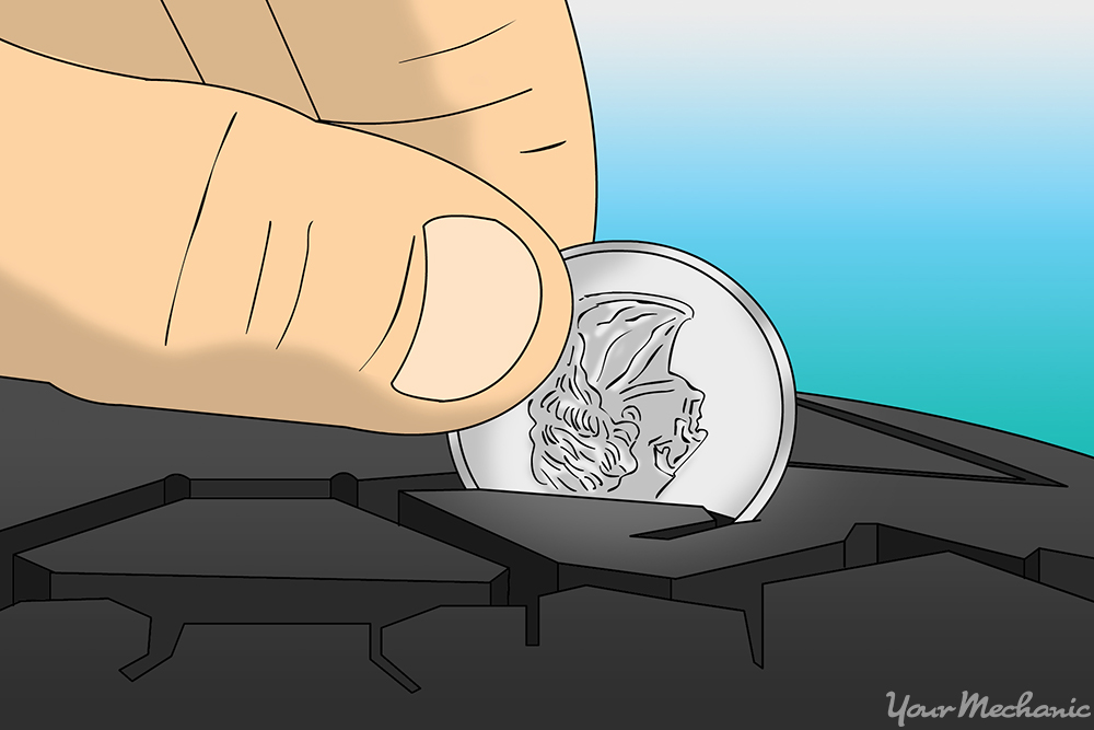 person using a quarter to check the tread on a car tire
