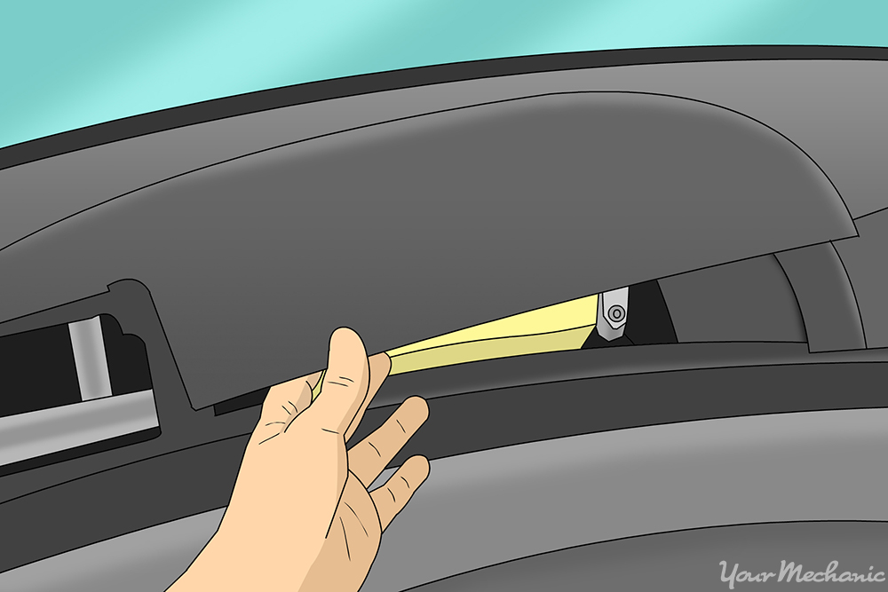 hand removing the panel above the glove box
