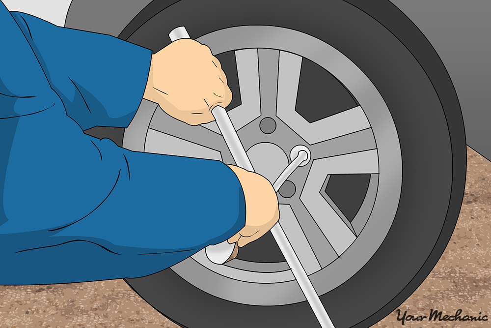 mechanic loosening lug nuts with 4-way lug wrench